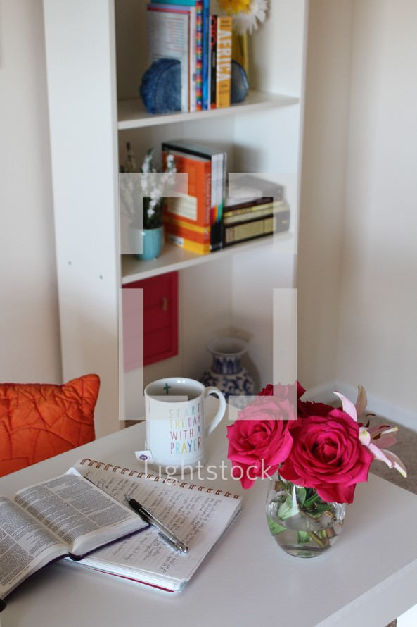red roses in a vase and open Bible on a table