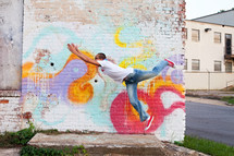 a man leaping in front of street art