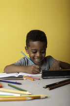 a boy child coloring on paper