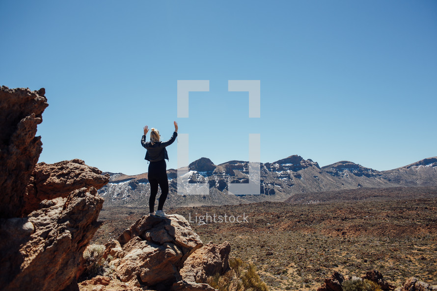 Woman standing on a rock in the dessert with raised hands