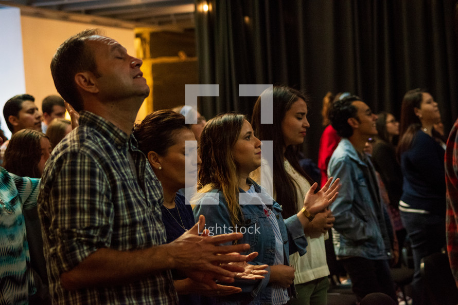 congregation with raised hands in worship during a worship service