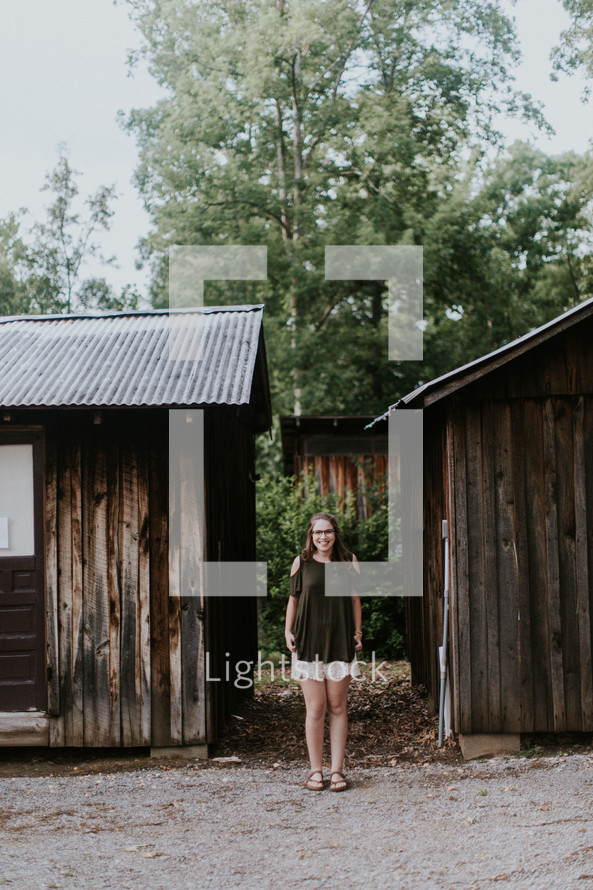 teen girl standing by cabins