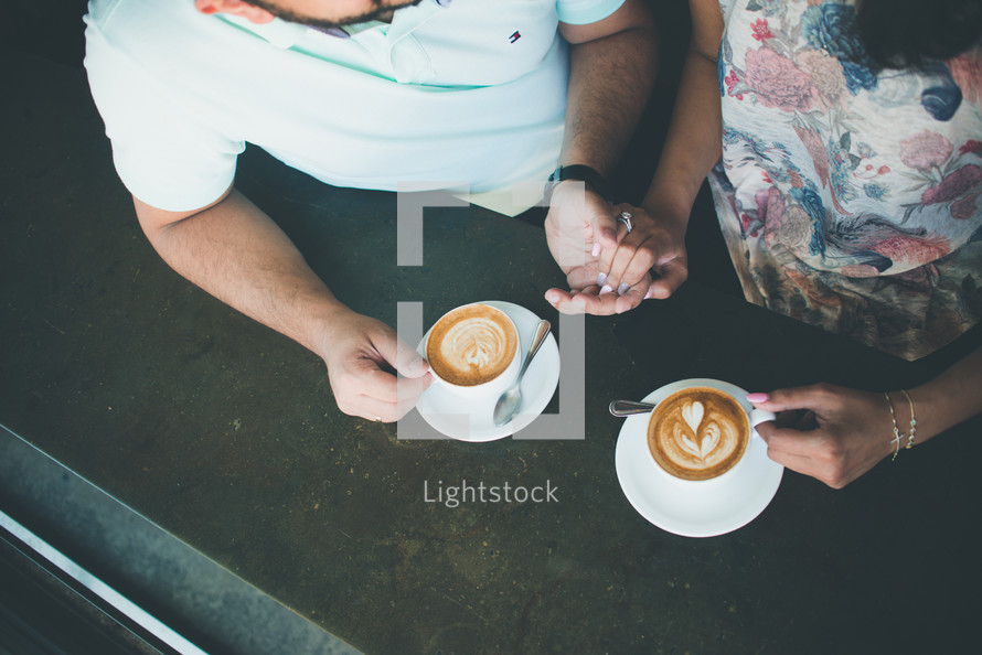 a couple holding hands and drinking coffee