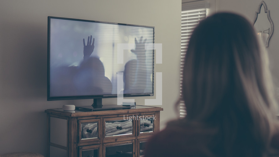 a woman watching a worship service streamed to her tv