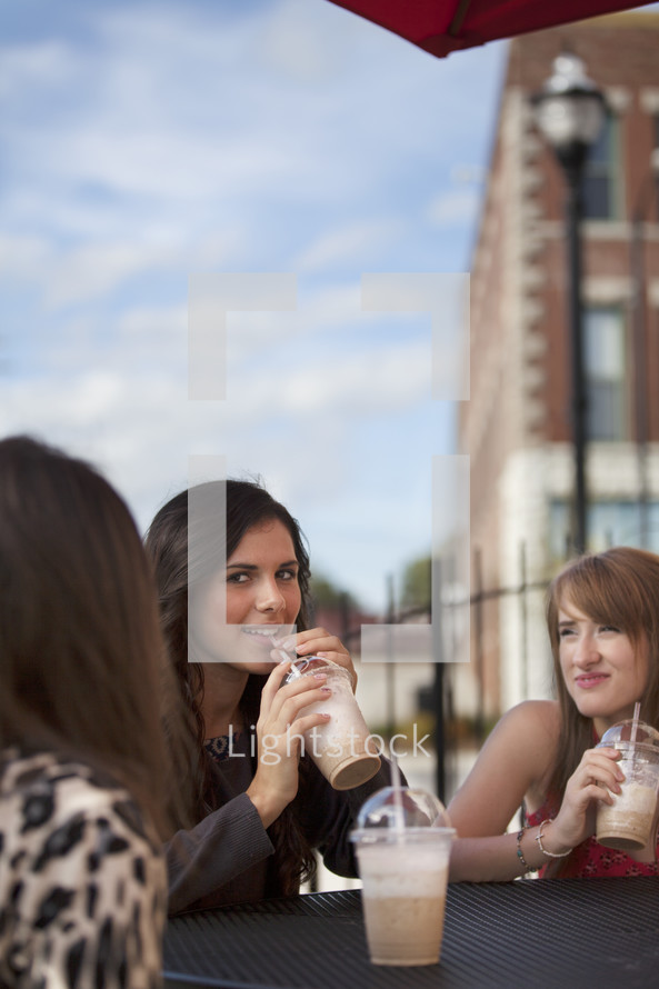 friends sitting at an outdoor table drinking milkshakes