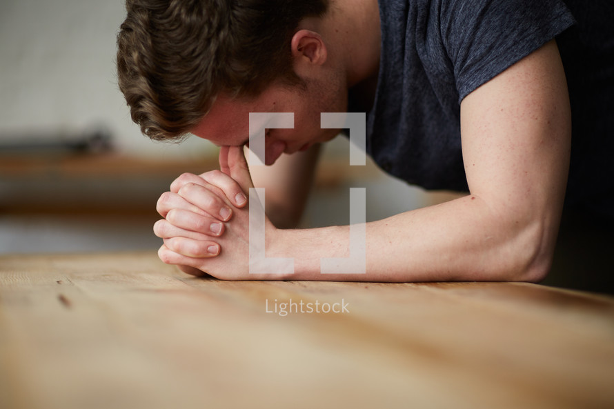 a man with his head on praying hands on a table