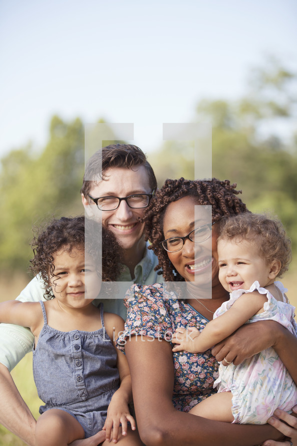 Multi racial family smiling outdoors on a sunny day.