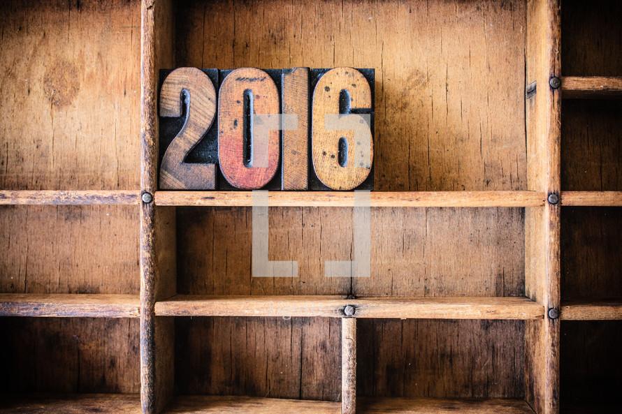 "Wooden letters spelling ""2016"" on a wooden bookshelf."