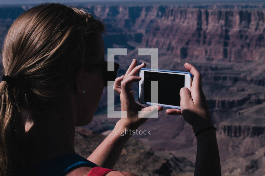 a woman taking pictures of a canyon with her cellphone