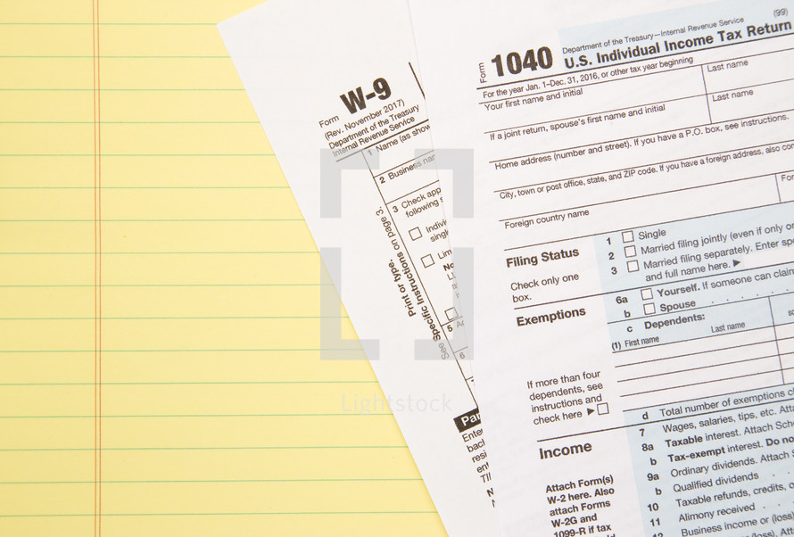 lined paper and W-9 and 1040 tax forms