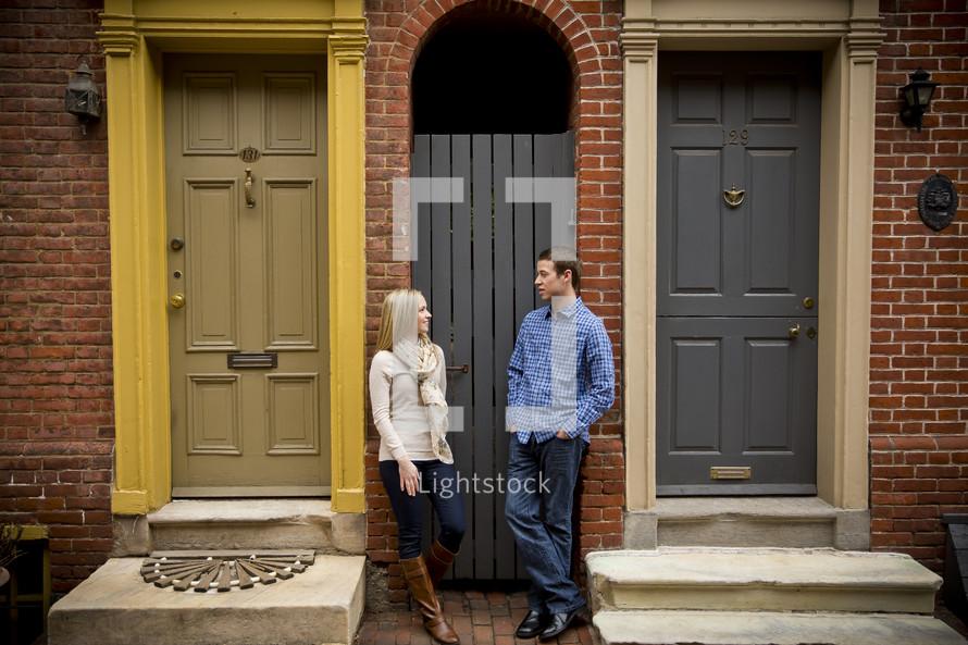 Woman and man standing between two doorways.