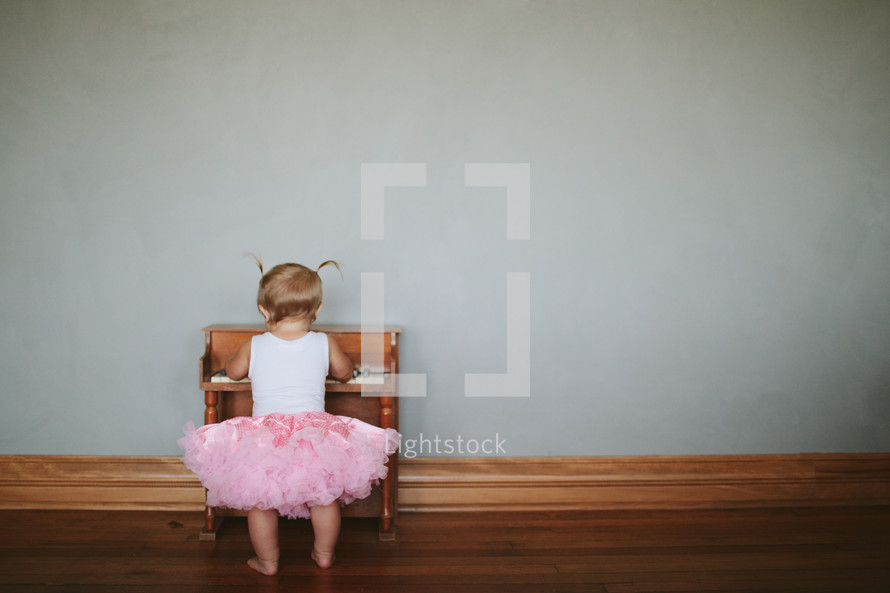toddler girl and a child's piano