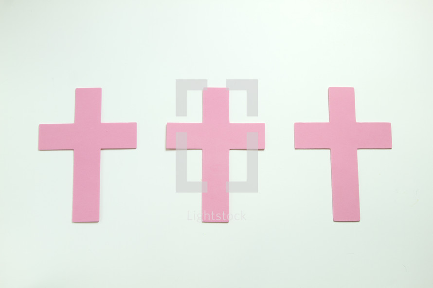 three pink crosses on a white background