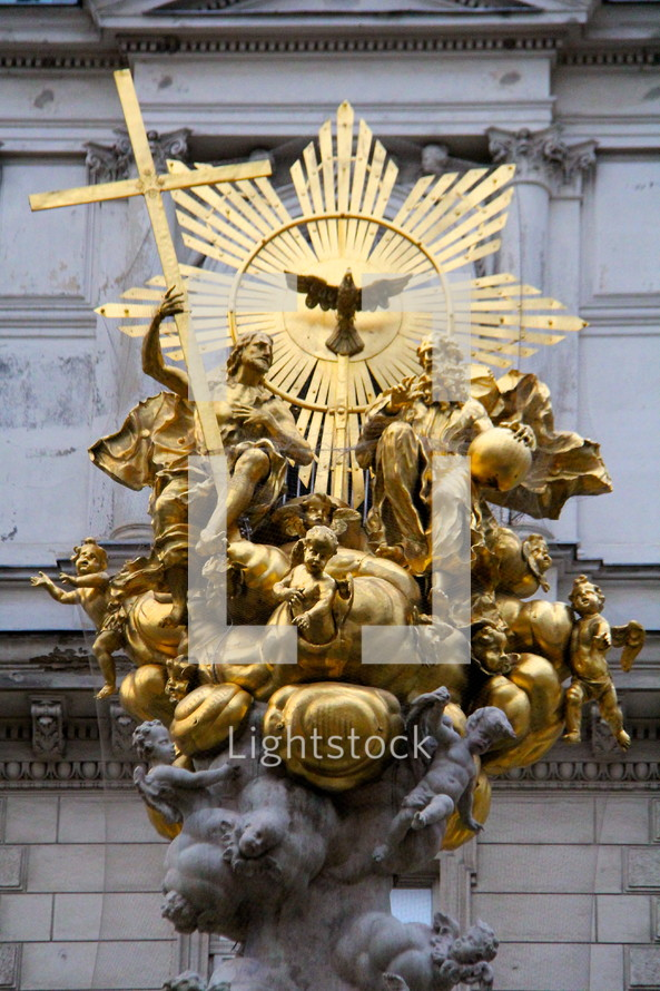 Golden statue depicting the Trinity : The Father, crucified Son and the Holy Spirit surrounded by the angelic host.