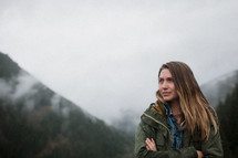 a woman with arms crossed over her chest standing in front of a foggy mountain