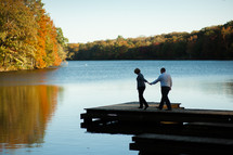 Couple walking on dock together with the fall colors over a lake.