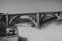 A bridge rises high below a raging river
