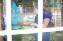 Women holding hands in prayer inside a window.