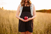 woman standing in a field cradling an apple