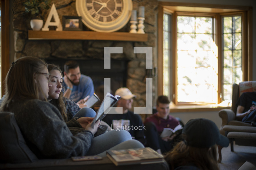 group of young adults sitting on a couch reading scripture