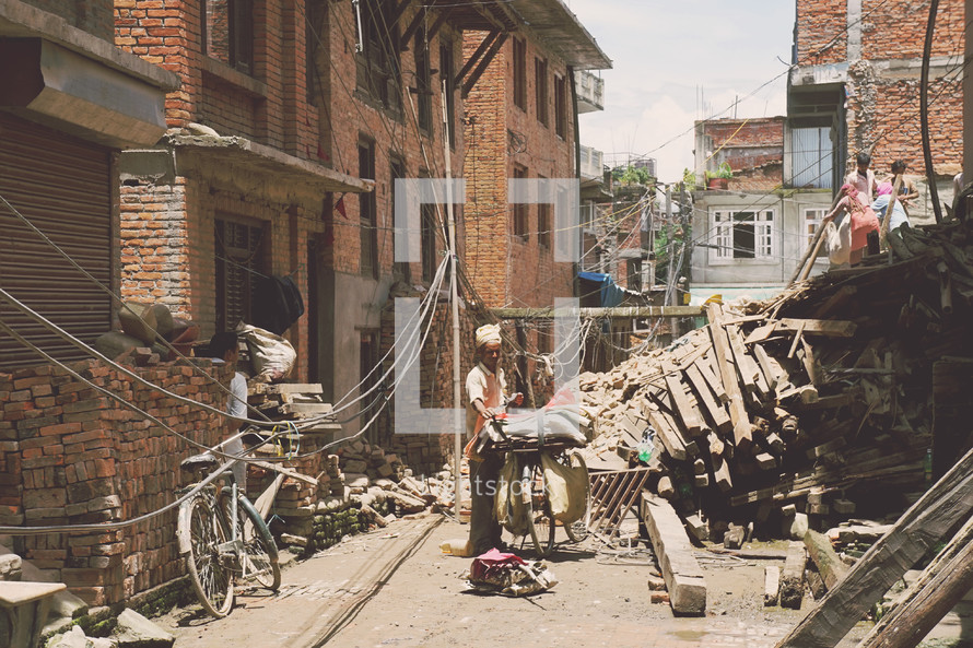 man standing in an alley next to a crumbled building