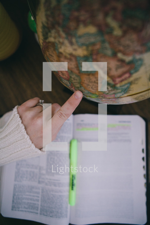 finger pointing to a globe and an open Bible