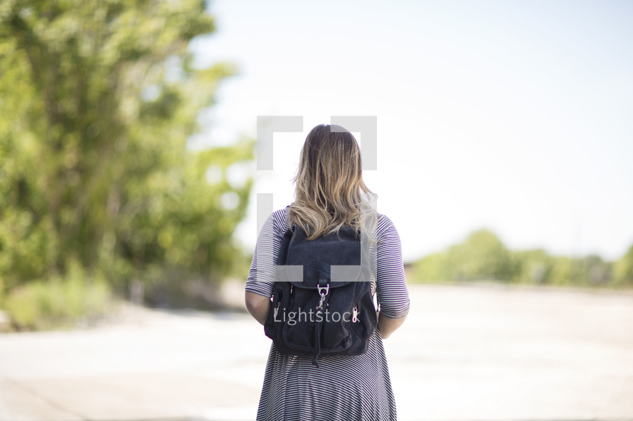 a woman with a book bag standing with back to the camera