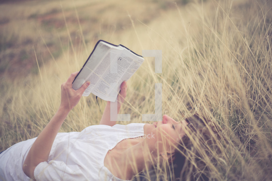 Woman laying in a field of grass reading the Bible.