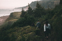 people hiking through a forest along a shore