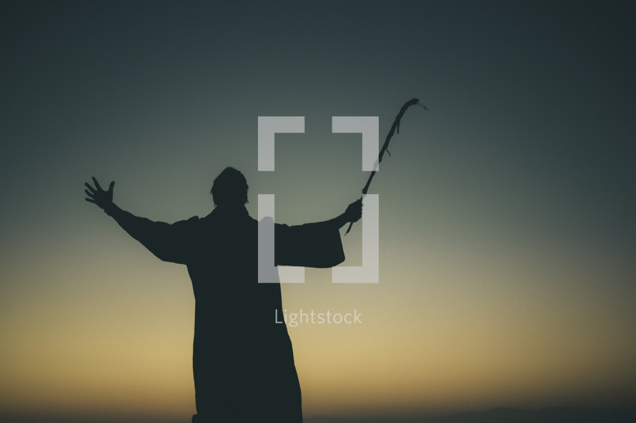silhouette of a man in a robe with a staff raised to the sky