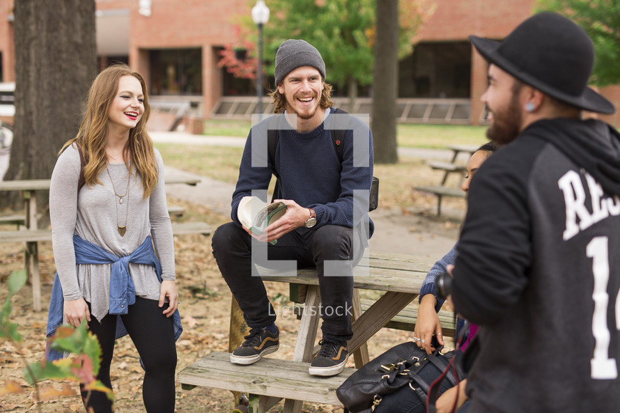 students gathered sitting around picnic table on campus