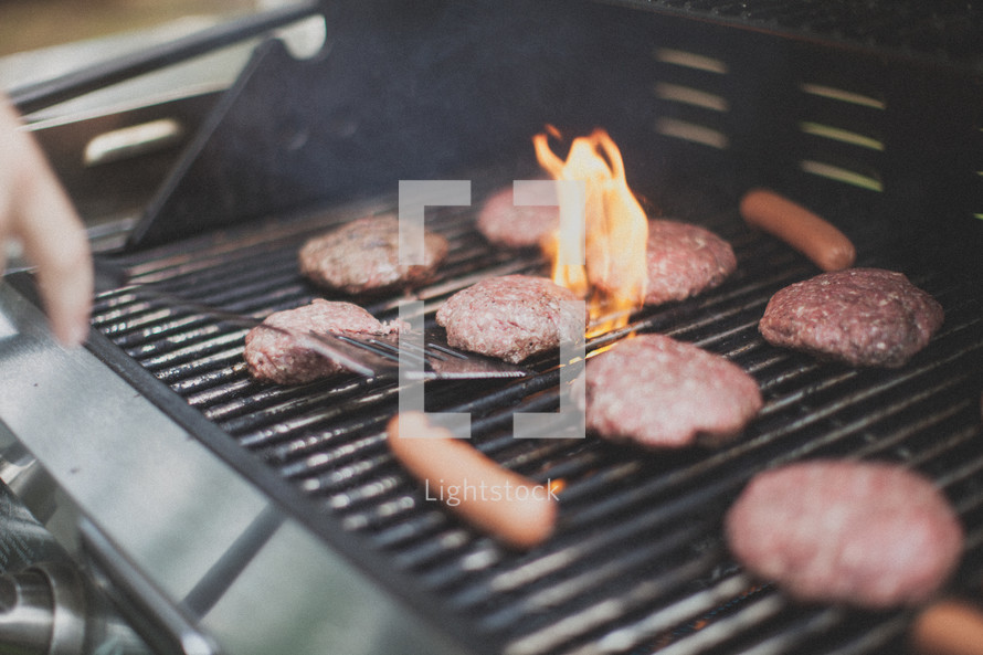 flipping hamburgers and hotdogs on a grill