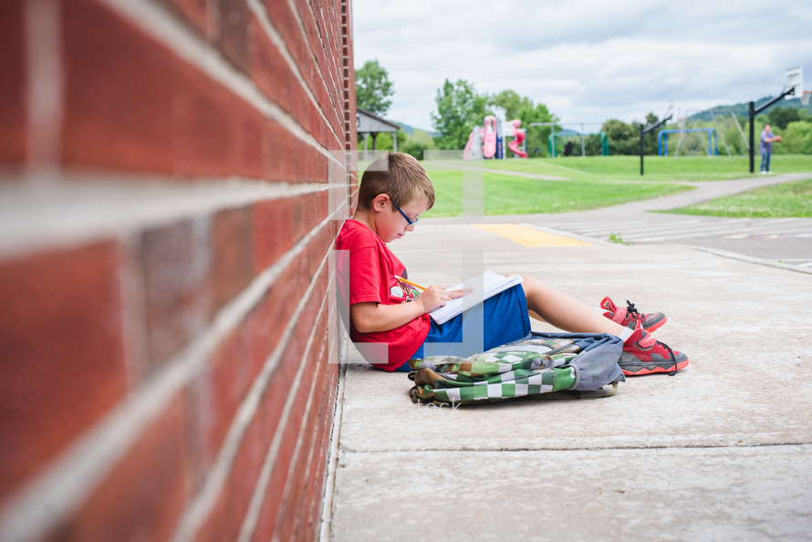 a boy doing his homework leaning against a school building