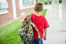 a boy carrying a book bag to school