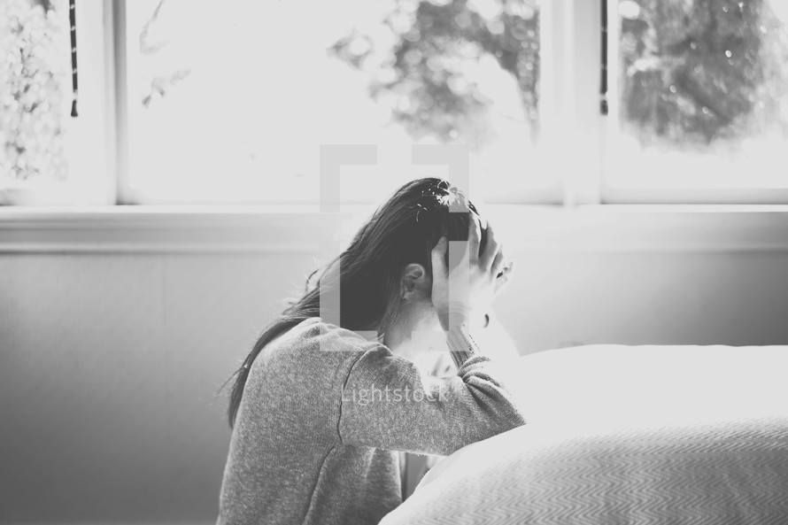 a woman crying by her bed