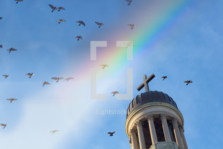 doves flying over a steeple and rainbow