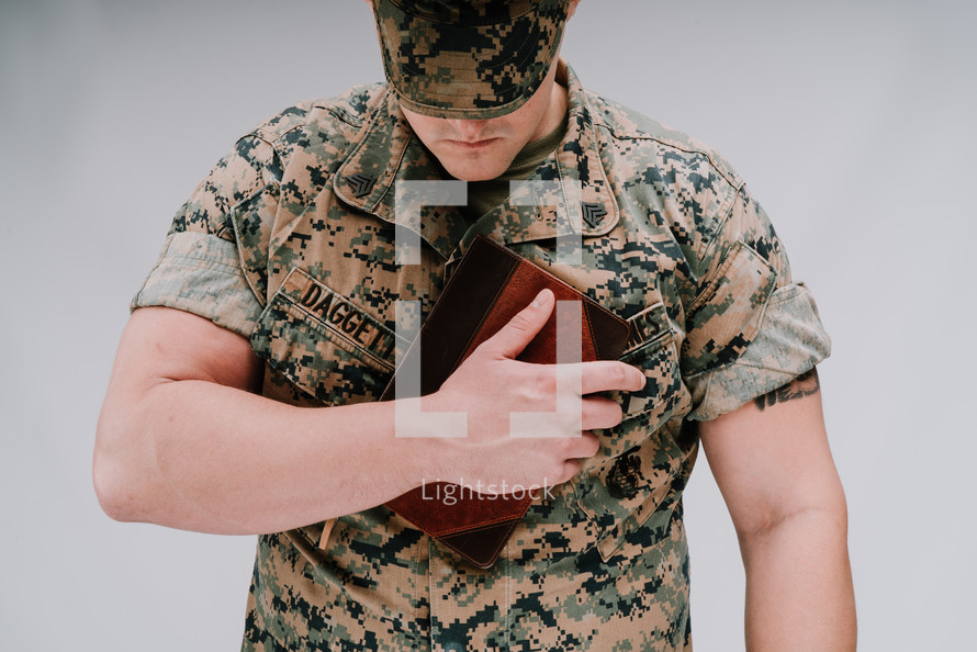 a marine holding a Bible against his chest