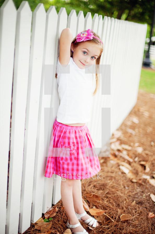 girl child in a gingham skirt standing in front of a white picket fence