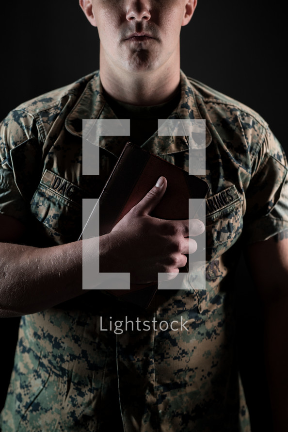 a serviceman holding a Bible against his chest