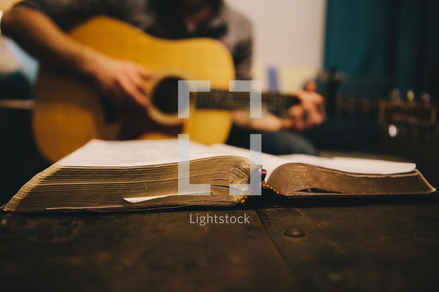 A man playing a guitar next to an open hymnal