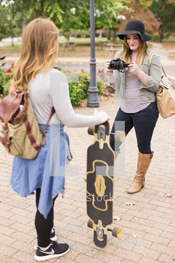 a teen girl holding a skateboard and a friend with a camera