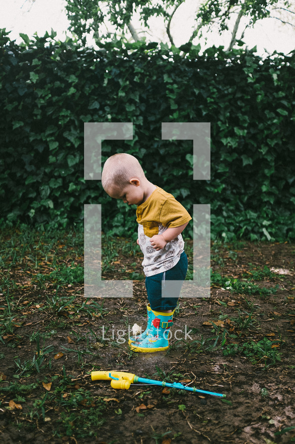toddler boy in rain boots in a backyard playing in mud
