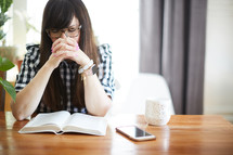 a woman sitting at a table praying over a Bible