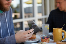 a man checking his cellphone over breakfast