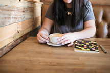 a girl with a journal and coffee cup sitting at a table