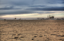 beach view of a factory with smoke stacks