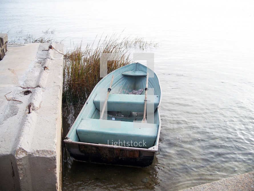 A rowboat with oars is parked dockside off the coast of St. Augustine, Florida where fishermen and vacationers often go out on the water for recreation and fishing.