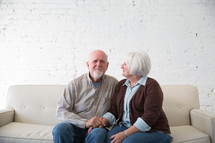 an elderly couple sitting on a couch holding hands