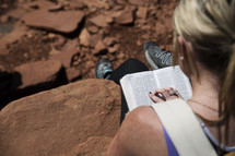 a woman sitting on a rock reading a Bible