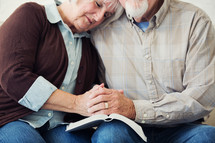 elderly couple holding hands and praying over the pages of a Bible